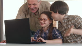 Senior man and his grandchildren entertain on laptop. Senior gray man and his grandchildren entertaining on laptop. Little brunette boy and his grandpa coming to stock footage