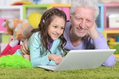 Senior man with his granddaughter using laptop Stock Photography