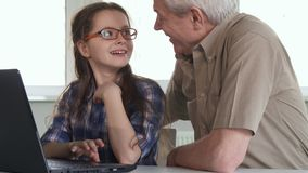 Senior man and his granddaughter watch something on laptop royalty free stock photography
