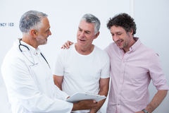 Senior man and his guardian talking to the doctor Stock Photography