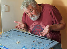 Senior man on his own angry doing a jigsaw puzzle. Royalty Free Stock Photography