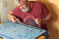 Senior man on his own difficult doing a jigsaw puzzle. A senior man sitting on his own having difficulty piecing together a jigsaw puzzle for entertainment Stock Photo