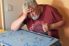 Senior man on his own difficult doing a jigsaw puzzle. A senior man sitting on his own having difficulty piecing together a jigsaw puzzle for entertainment Stock Photography