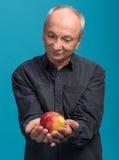 Senior man holding an apple Stock Photos