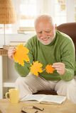 Senior man holding autumn leaves. Smiling happily, sitting in living room with book Royalty Free Stock Images