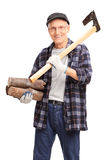 Senior man holding and axe and a bunch of logs Royalty Free Stock Images