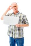 Senior man holding a blank placard and scratching his head Royalty Free Stock Photos