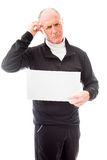 Senior man holding a blank placard and scratching his head Royalty Free Stock Image