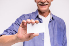 Senior man. Is holding blank visiting card royalty free stock image