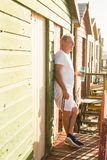 Senior man holding bottle while standing at beach hut Royalty Free Stock Image