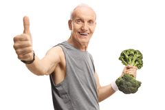 Senior man holding a broccoli dumbbell and showing thumbs up royalty free stock image