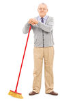 Senior man holding a broom. Full length portrait of a senior man holding a broom isolated on white background Royalty Free Stock Photo