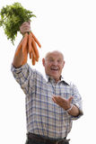 senior man holding bunch of carrots in the air, cut out Royalty Free Stock Photography