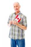 Senior man holding a Canadian flag Stock Photos
