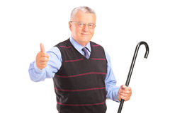A senior man holding a cane and giving thumb up Stock Images