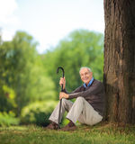 Senior man holding a cane and sitting on grass in park Stock Photos