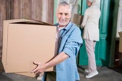Senior man holding cardboard box and smiling at camera. Happy senior men holding cardboard box and smiling at camera Royalty Free Stock Photos