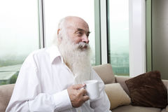 Senior man holding coffee cup at home Royalty Free Stock Images