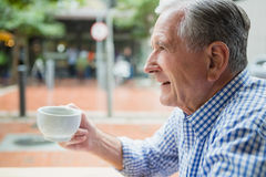 Senior man holding a coffee cup. In outdoor cafe Royalty Free Stock Image