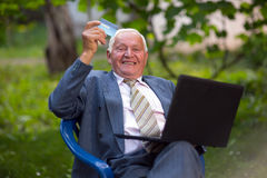 Senior man holding credit card outdoors Stock Image