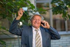 Senior man holding credit card outdoors, laughing Royalty Free Stock Photos