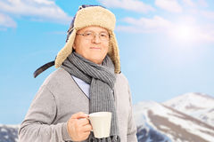 Senior man holding a cup in front of snowy mountain Stock Photos