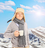 Senior man holding a cup in front of snowy mountain Stock Images