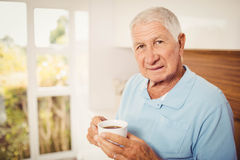 Senior man holding cup and looking at the camera Stock Image