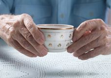Senior man holding cup of tea in their hands at table close-up Royalty Free Stock Photography