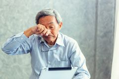 Senior man is holding eyeglasses and rubbing his tired eyes whi. Le reading e-book in tablet stock photo
