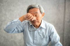 Senior man is holding eyeglasses and rubbing his tired eyes whi. Le reading e-book in tablet royalty free stock photo