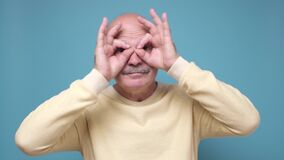 Senior man holding fingers near eyes like glasses or mask like super hero.