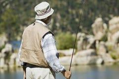 Senior Man Holding Fishing Rod. Rear view of Hispanic senior man standing with a fishing rod Stock Image