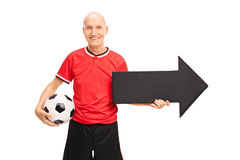 Senior man holding football and a black arrow Royalty Free Stock Image