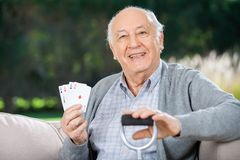 Senior Man Holding Four Aces While Sitting On Royalty Free Stock Photos