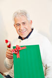 Senior man holding gift at christmas Royalty Free Stock Photos