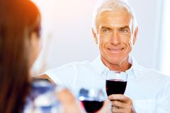 Senior man with holding a glass of wine indoors. Portrait of a handsome senior with a glass of red wine royalty free stock photo