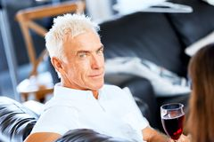 Senior man with holding a glass of wine indoors. Portrait of a handsome senior with a glass of red wine stock images
