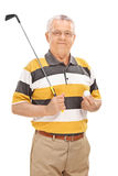Senior man holding a golf club and a ball Stock Image