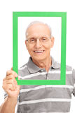 Senior man holding a green picture frame Stock Photos