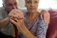 Senior man holding hands of old woman with walking stick in living room Royalty Free Stock Photography