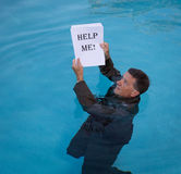 Senior man holding help me paperwork in water Stock Images