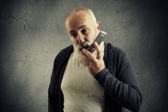 Senior man holding his cellphone and screaming Stock Photo