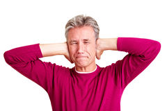 Senior man holding his ears. Frustrated senior man closing his ears with his hands Royalty Free Stock Photo