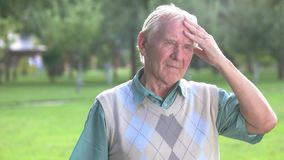 Senior man holding his forehead. Older person with gray hair. Looking back at the past. Deeds and consequences stock video