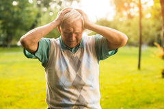 Senior man holding his head. Royalty Free Stock Image