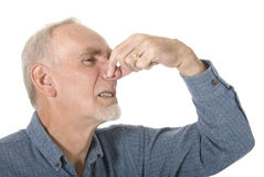 Senior man holding his nose. Studio shot of senior man on white background holding his nose against bad smell stock photo