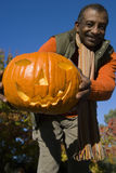 Senior man holding jack-o-lantern Stock Images