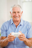 Senior man holding joystick and looking at camera Royalty Free Stock Image
