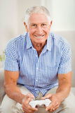 Senior man holding joystick and looking at camera Stock Photo